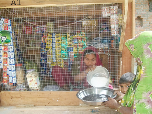 Graphic: Seemadevi handing goods to customers in her shop