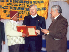 Mr. Babooja Ranjan Choudhary receiving international award for the best Braille essay at a public function organized by All India Confederation of the Blind on the occasion of 202nd Birth Anniversary of Louis Braille